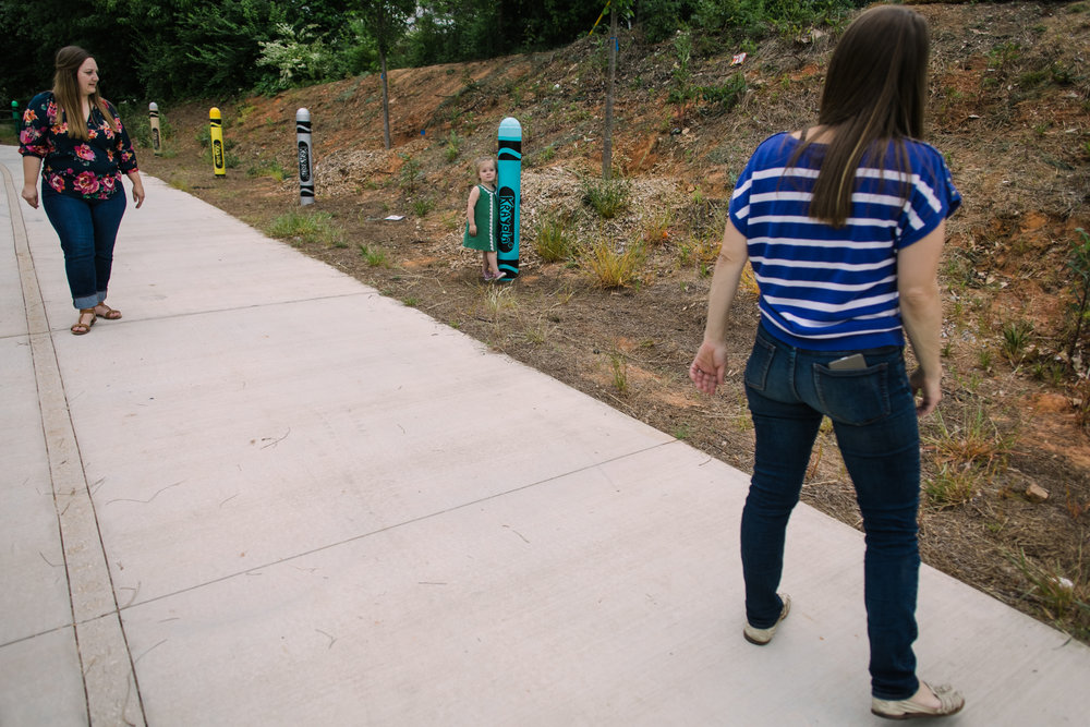 a child stands by a crayon post on a path as her aunt and mother look at her