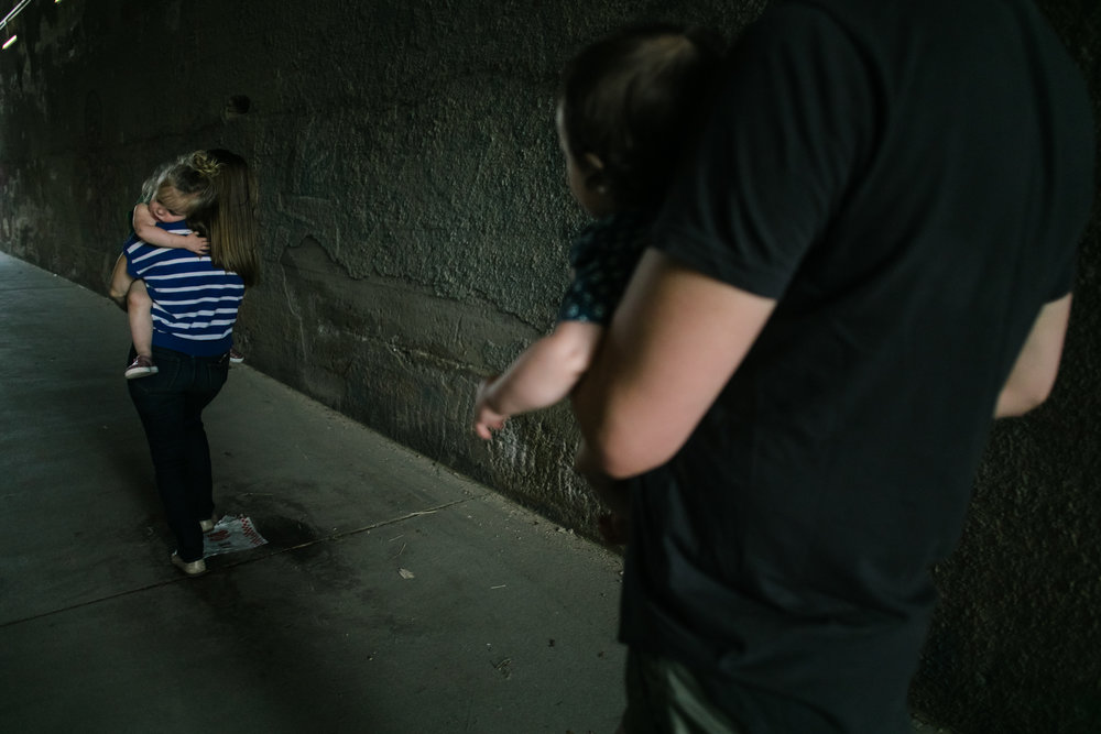 a child lies on her mother while walking through a tunnel