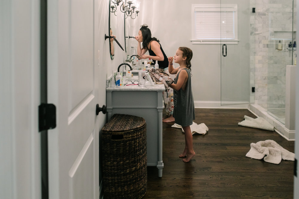 a young girl stands on her tippy toes to look at herself in the mirror to put on makeup while her mom is putting on makeup in the background