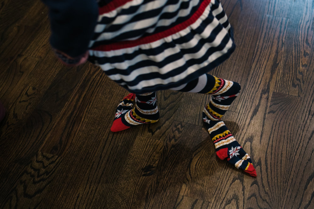 A young girl walks on hardwood floors with tights not pulled on all the way during documentary family photography session