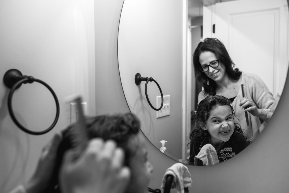 a young girl makes a funny face in the mirror as her mom combs her hair during a documentary family photography session