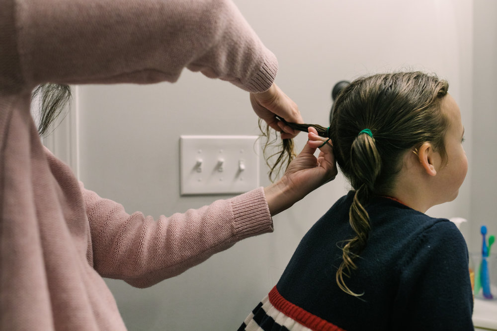 A mother puts her daughter's hair in pigtails during a documentary family photography session