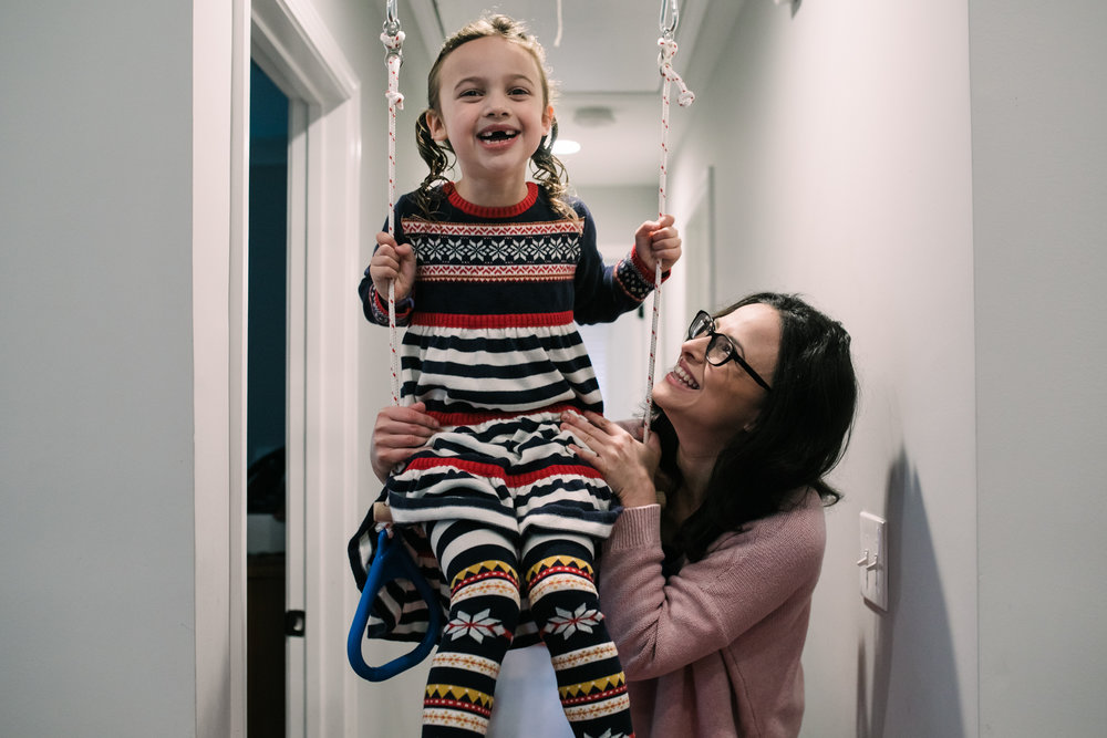 A young girl sits on a swing in her house while her mom holds the swing and looks up at her during a documentary family photography session