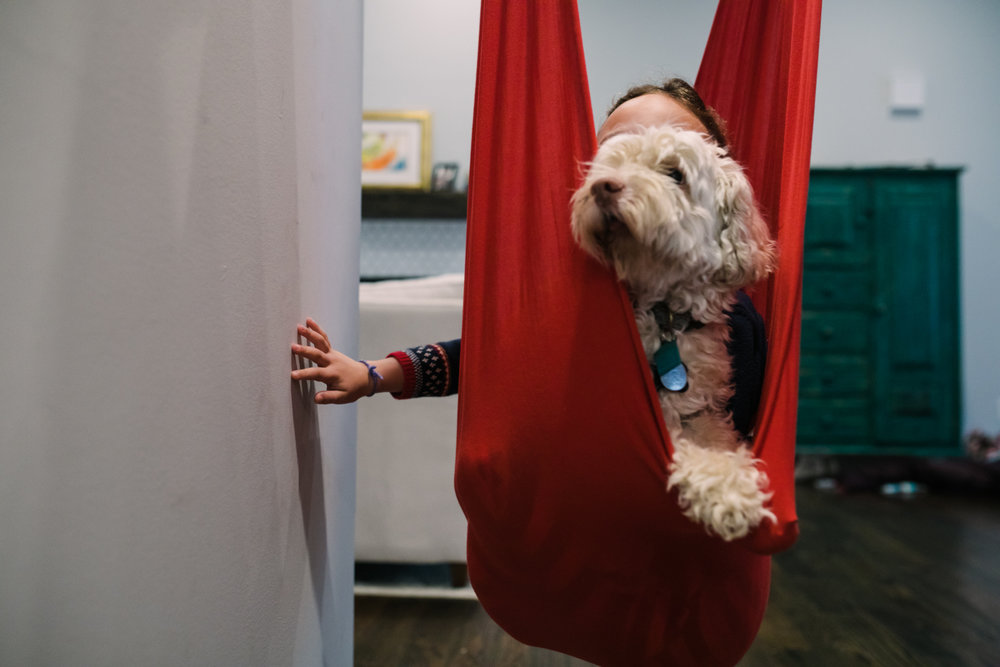 A girl puts her hand against a wall to push she and her dog in a red swing during a documentary family photography session
