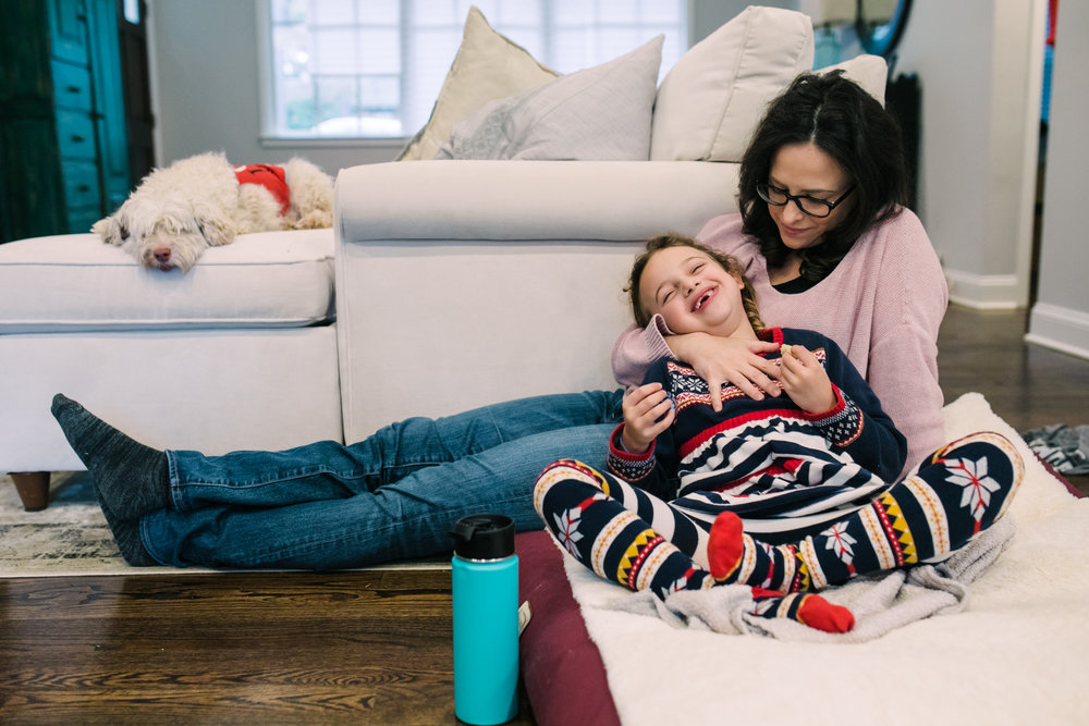 a young girl lies back on her mother as they sit together on the ground as a small dog lounges on the couch behind them during a documentary family photography session