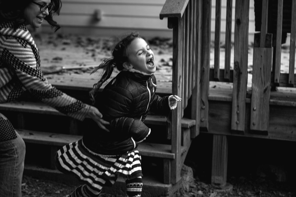 a girl laughs as her mom tags her during a game of chase during a documentary family photography session