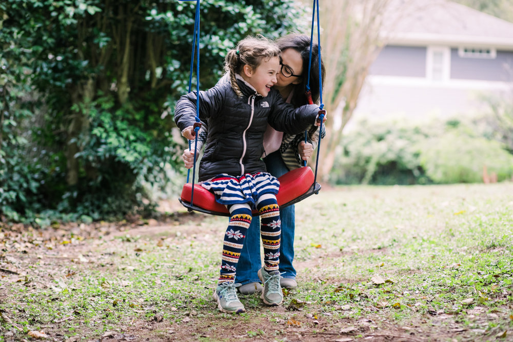 A mom whispers into her daughters ear while she is on a swing during a documentary family photography session