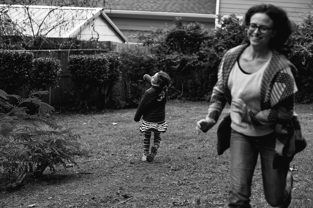 A girl runs in on direction as her mother runs in another direction during a game of chase during a documentary family photography session