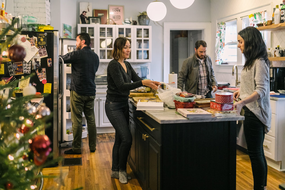 Two women prepare food at a kitchen island while a man reaches into a fridge behind them and another man walks towards them