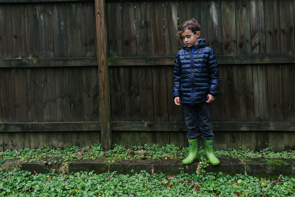 A boy stands on a ledge in front of a fence looking down at the grass that matches his boots