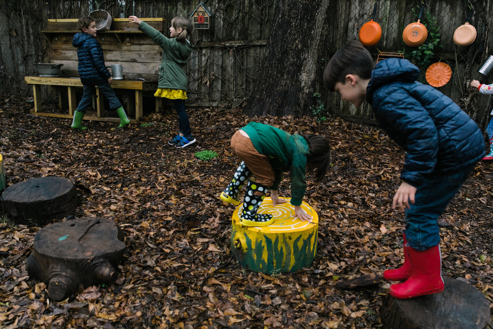 A boy bends over on a stump as another boy prepares to jump off another stump while a boy and a girl play behind them