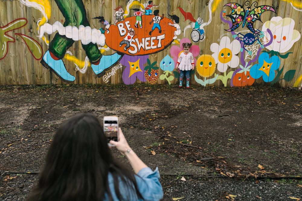 A child poses at a mural while her mom takes her picture with a phone
