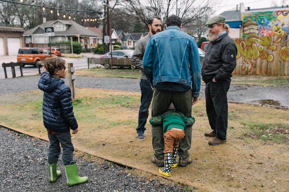 A boy puts his head through his dad's legs as two men stand nearby
