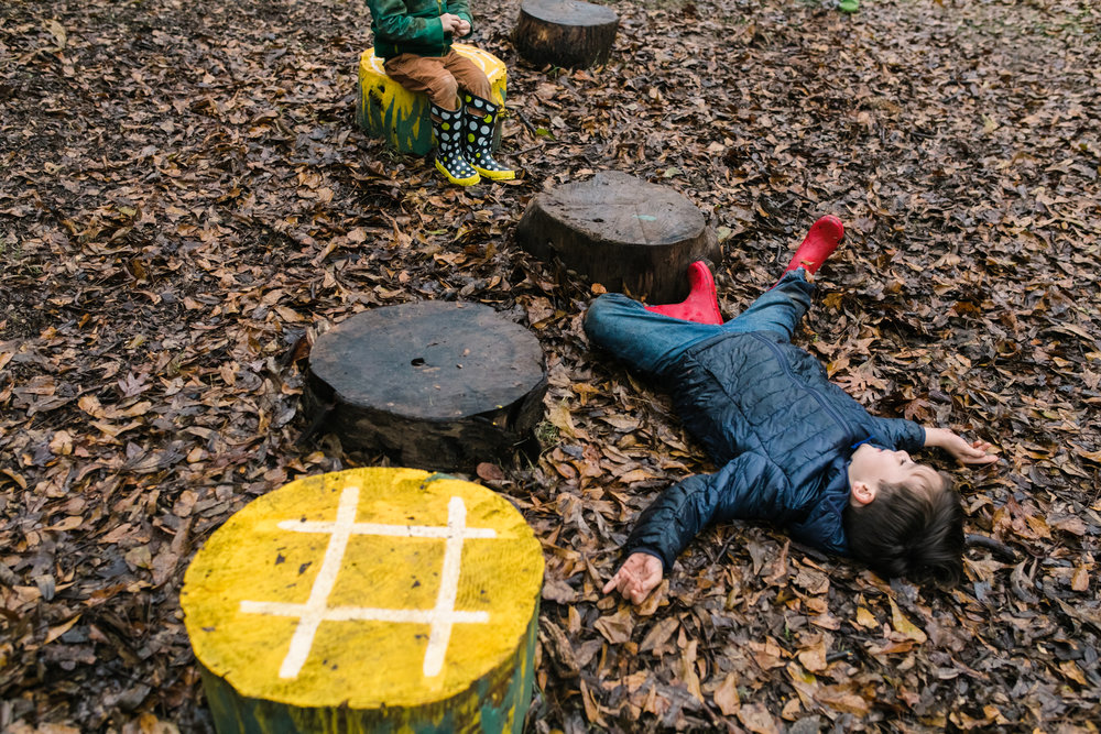 A boy lies on the ground and another child sits on a stump in the distance