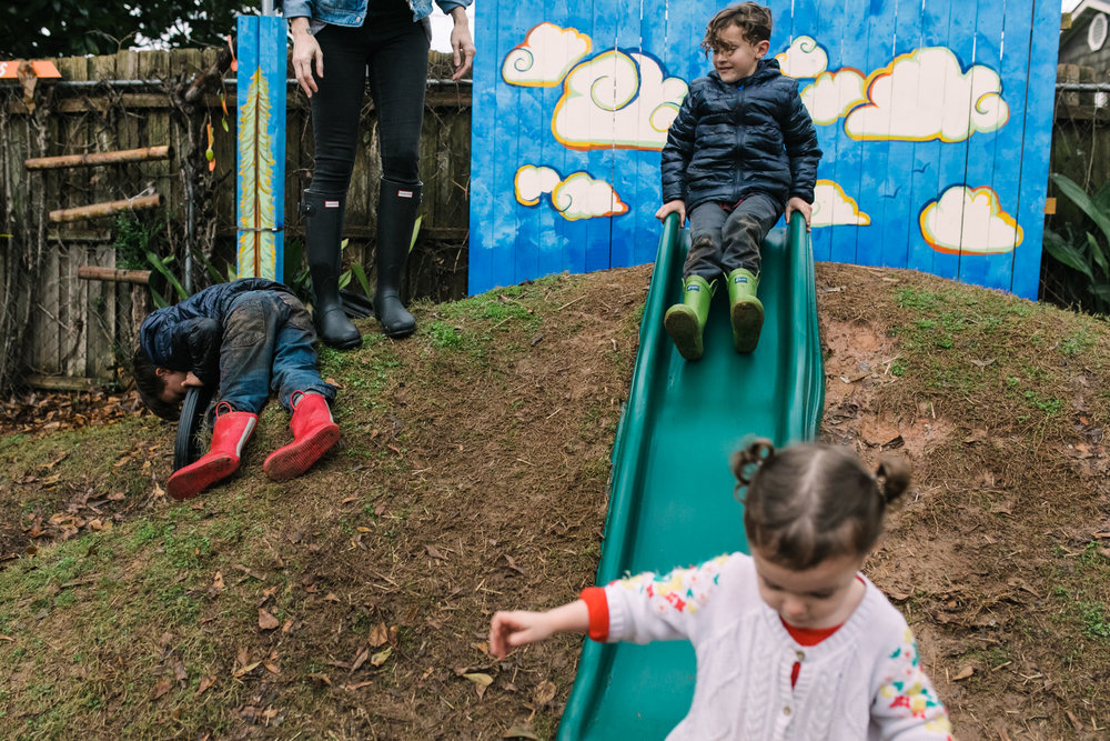 3 children play on and around a slide while their mother stands near them