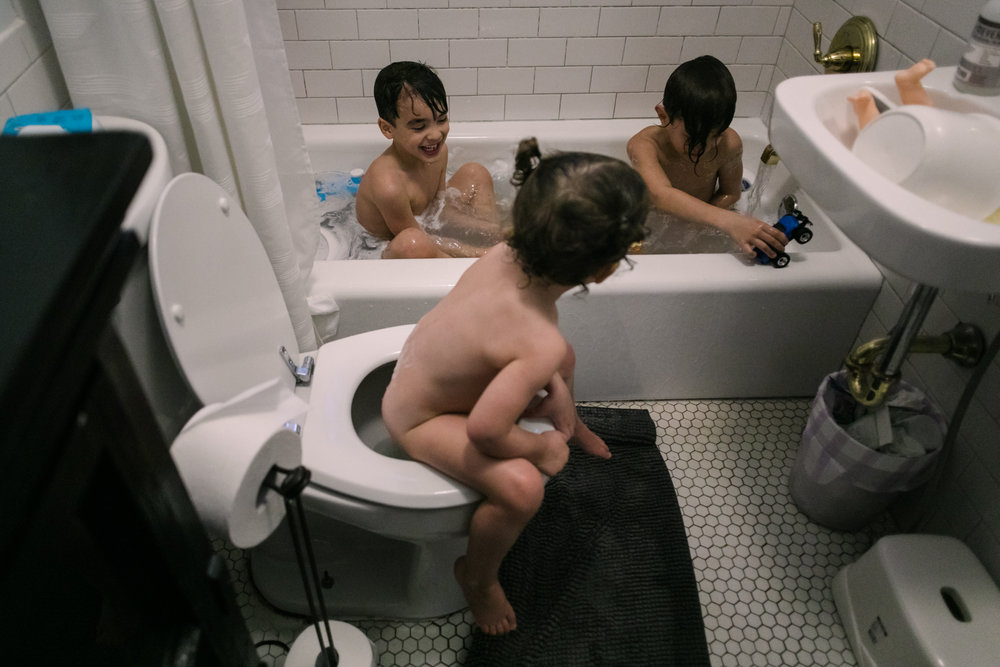 a child sits on the toilet and watches her brothers play in the bathtub
