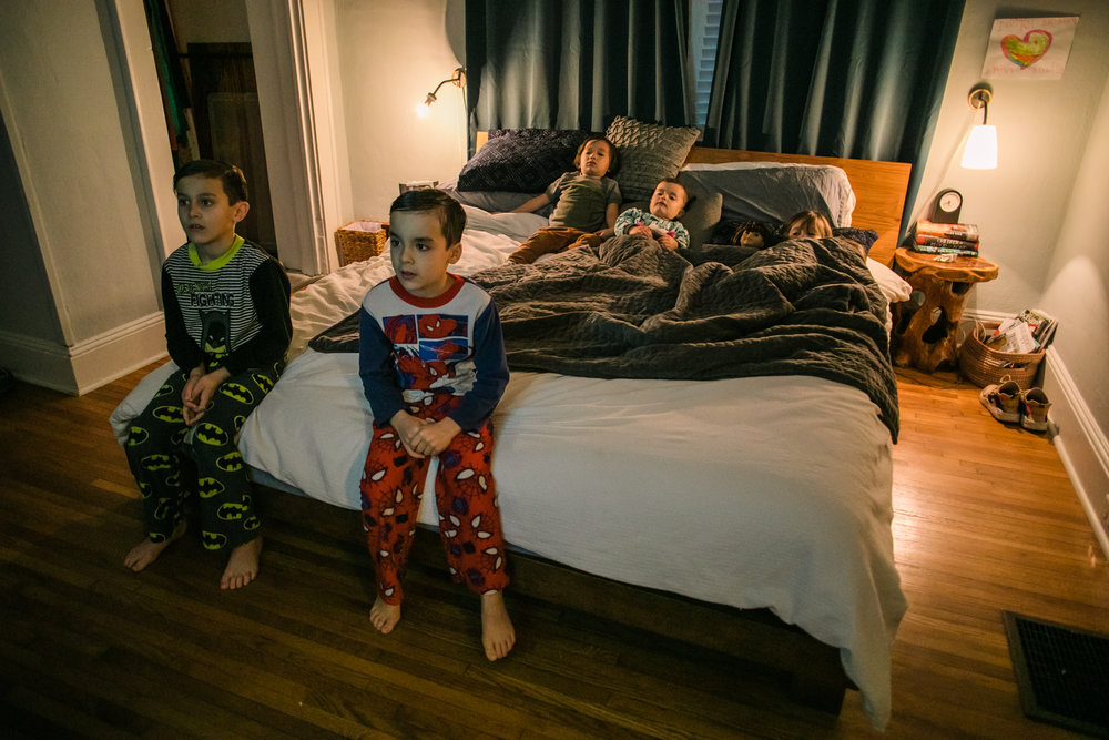 5 children sit on a bed in their pajamas watching tv