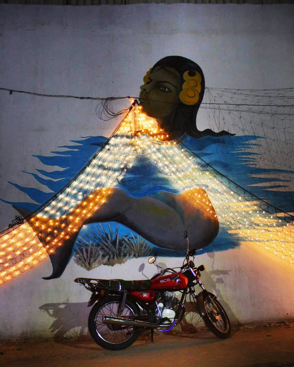 Motorcycle resting against a mural in a city fair in Port Sudan, Sudan. By Najla Salih.