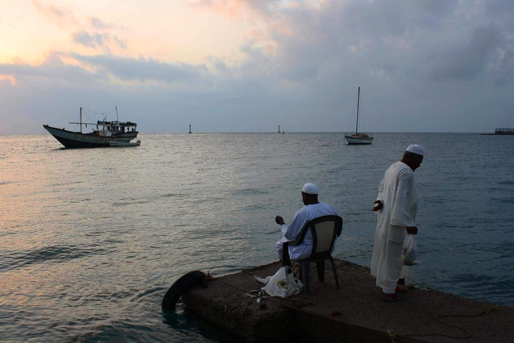 Men watching the sunrise at the harbour in Port Sudan, Sudan. By Najla Salih.