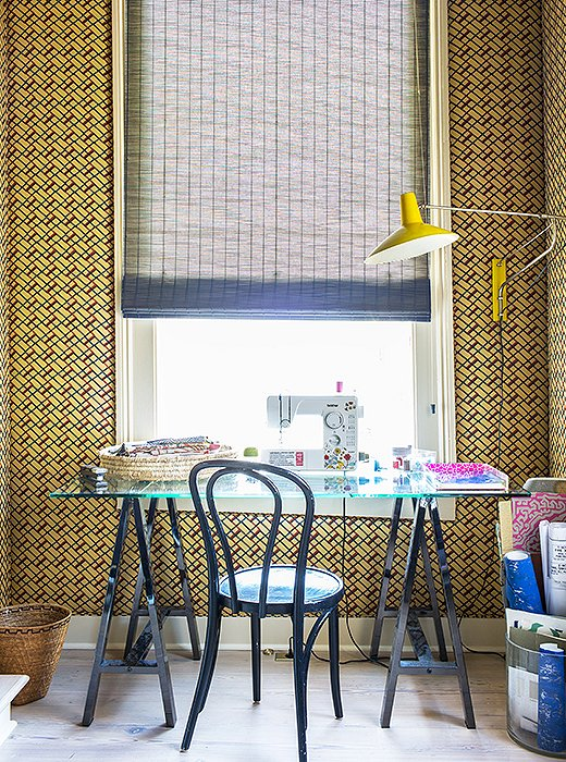 "Just as the trellis room downstairs is visible from the front door, Kiki's sewing room, directly above it, is visible from the top of the stairs. ""I like to max out these focal-point rooms."" Sara turned this small space into a statement by covering the walls in Muriel Brandolini fabric."