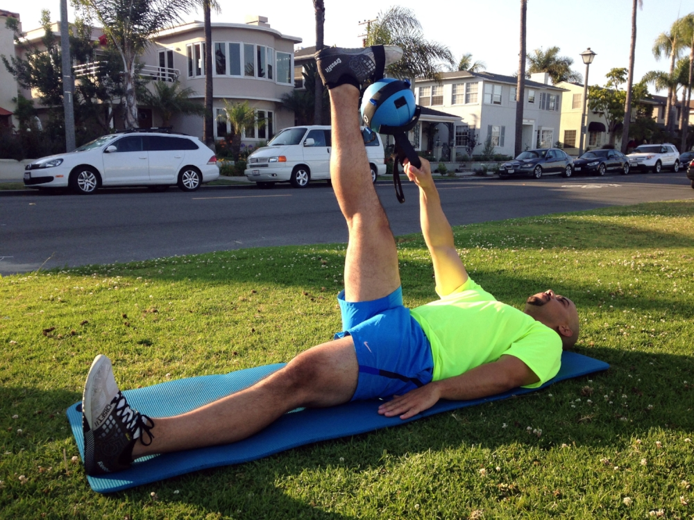 This hip mobility stretch uses the Gravity Ball's loop straps and is very beneficial for easing lower back tightness and pain. Slip one foot through a loop strap. While lying on your back slowly lift the leg straight up until it's straight or as close to straight as possible. Bend the leg that remains on the ground for a modified version of the stretch.