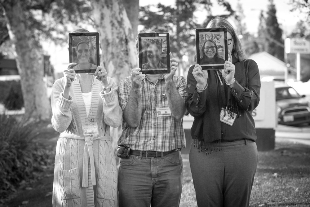 Emily Blaney, Jeff Watts, Jamie Lewsadder holding iPads over their faces