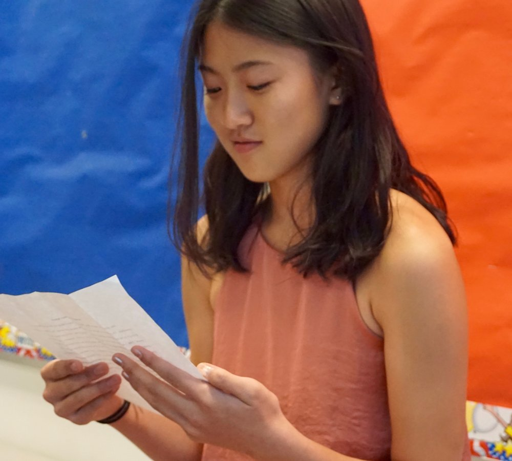 Girl reading from a paper.