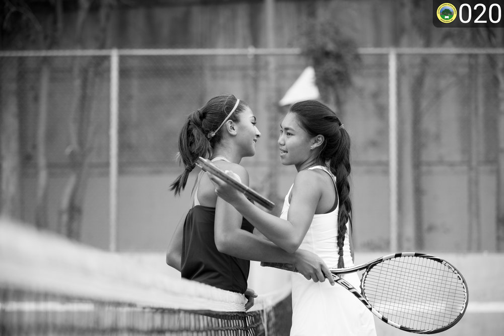 Two tennis players hugging over the net.