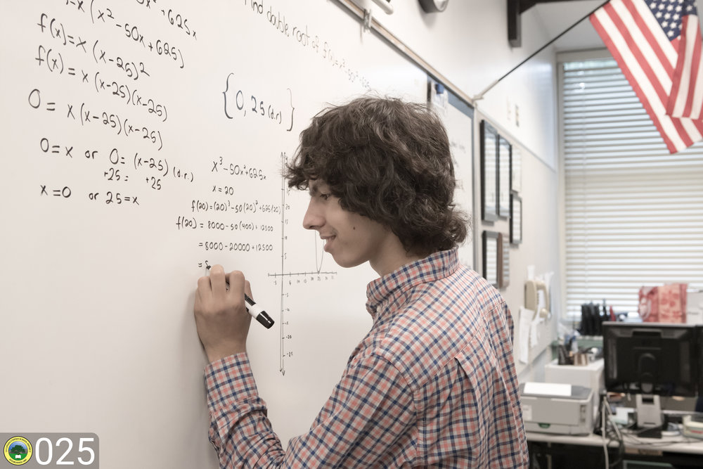 LCHS student solves math problem on white board.