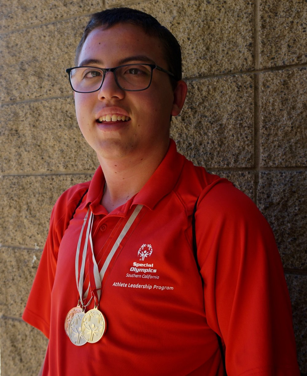 Autistic boy wearing a bronze, silver, and gold medals.