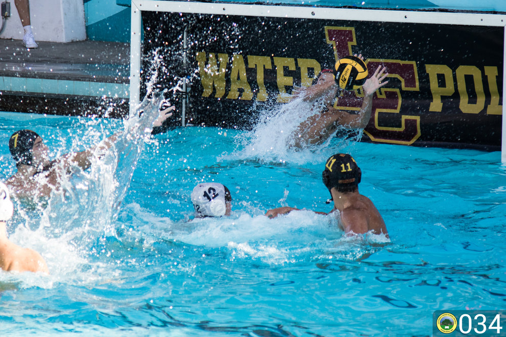 Spartan water polo goalie jumping for the ball.