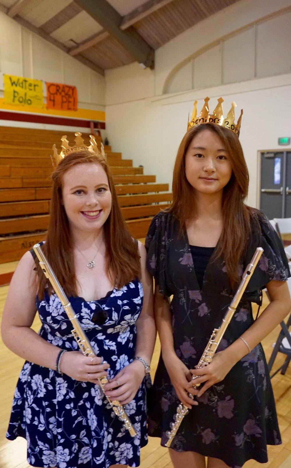 Two seniors pose with flutes