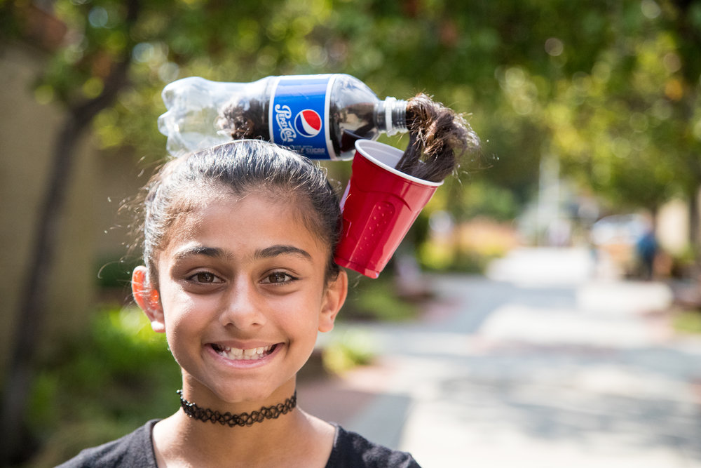 Young girl with hair in soda bottle being poured in a cup.