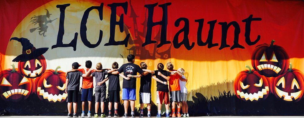 Young boys standing in front of LCE Haunt backdrop.