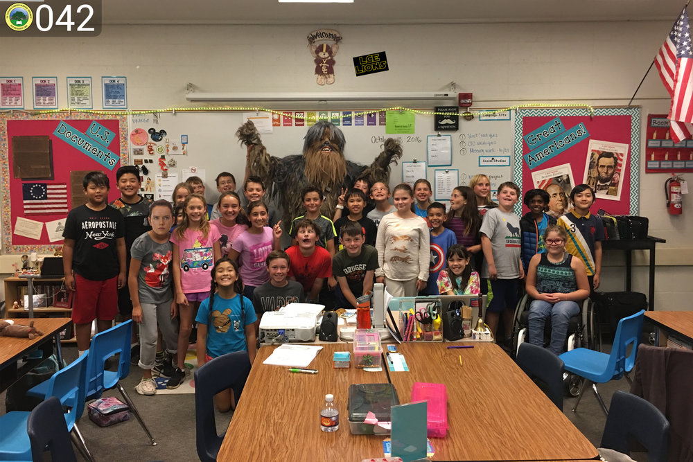Young students posing with chewbacca for a photo.