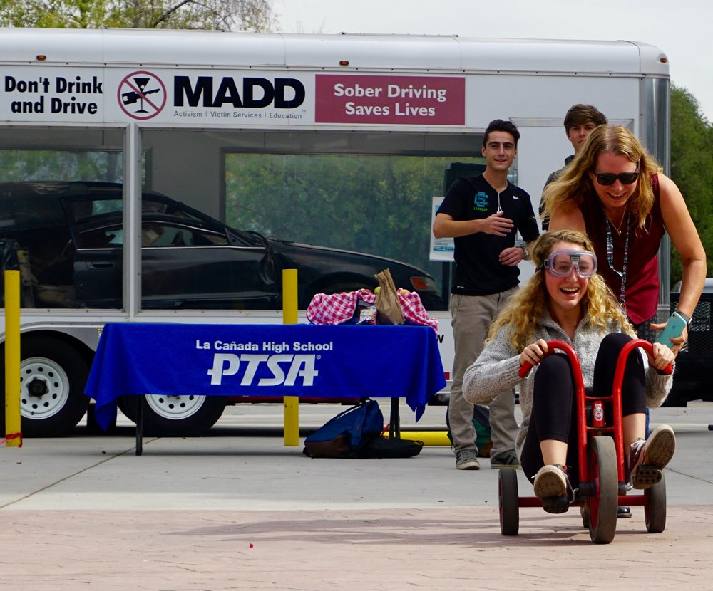 Jamie Lewsadder pushing girl on bike who's wearing alcohol impairment simulation googles