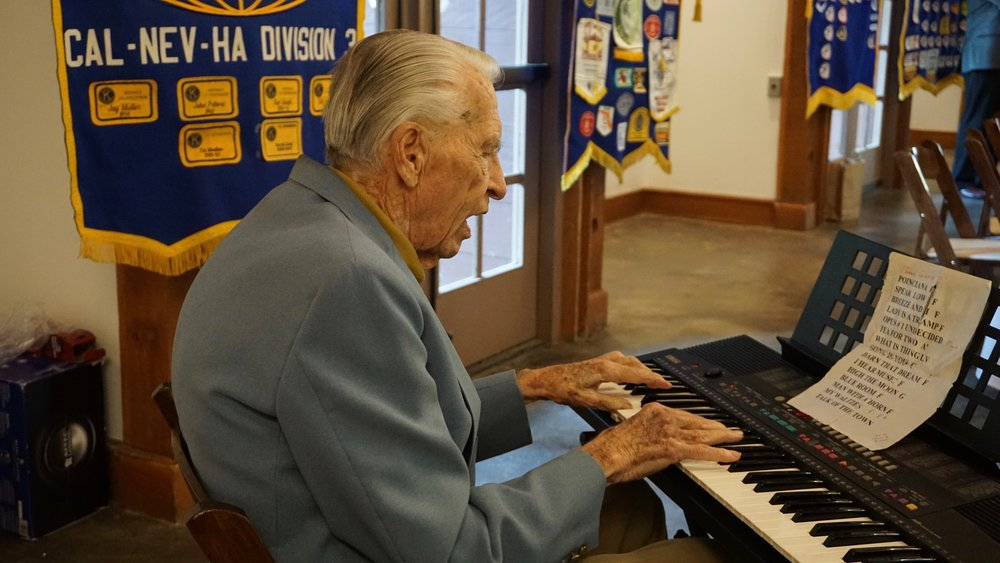 Older man playing the keyboard for a Kiwanis meeting.