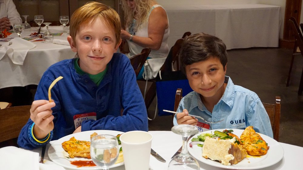 Two young boys enjoying lunch.