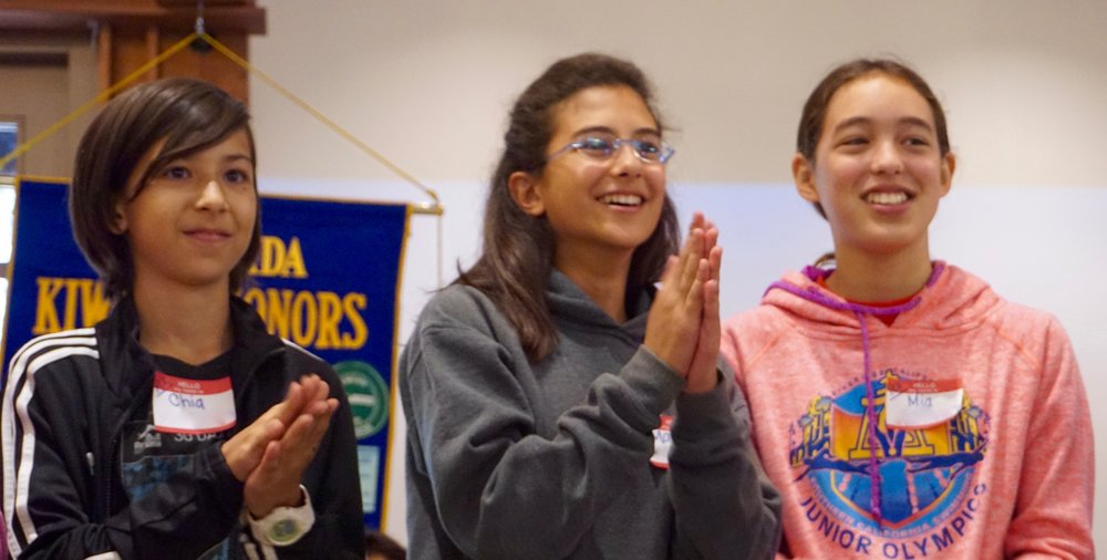 Three young girls participating in the the Kiwanis meeting.