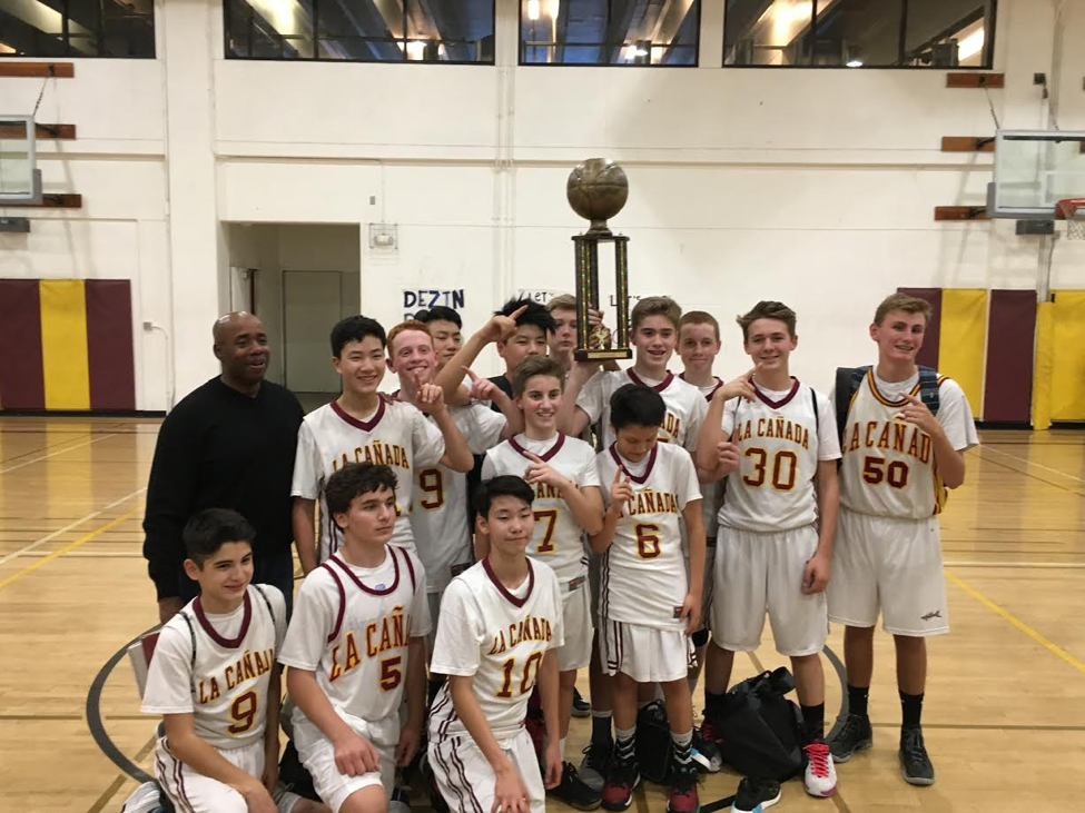 8th grade boys basketball team holding championship trophy.