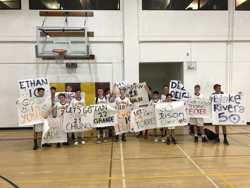 8th grade boys basketball championship team holding posters with their name on it.