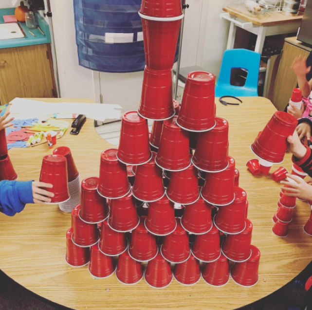 Red cups stacked on table.