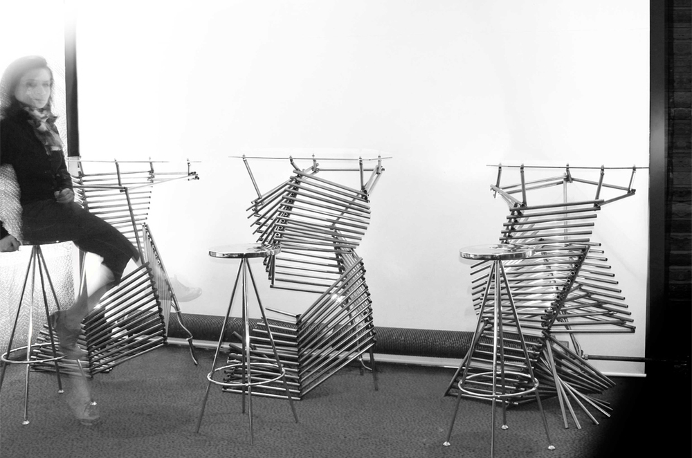 "50°6° Tables | for AAIS | London [2011]   For each table, less than 100 sections of pipe were assembled to form each table such that it reached a height of 42"" and a weight less than 75 lbs. The individual stock pieces were welded according to a folding logic inspired by oragami techniques. Using the 3 custom jigs, unique V-shaped angled components were fashioned. Those components were then slotted into one another via the jig's spacing system to reach the desired height. The two part process produced 3 different spiralling towers of steel that were then capped with a piece of custom cut glass to fit the geometry of the top most plane. The tables were designed for and featured in Angles of Incidence in Köln, Germany in 2012. The were also featured at the Nigerian House during the Summer Olympics in London 2012 (above picture)."