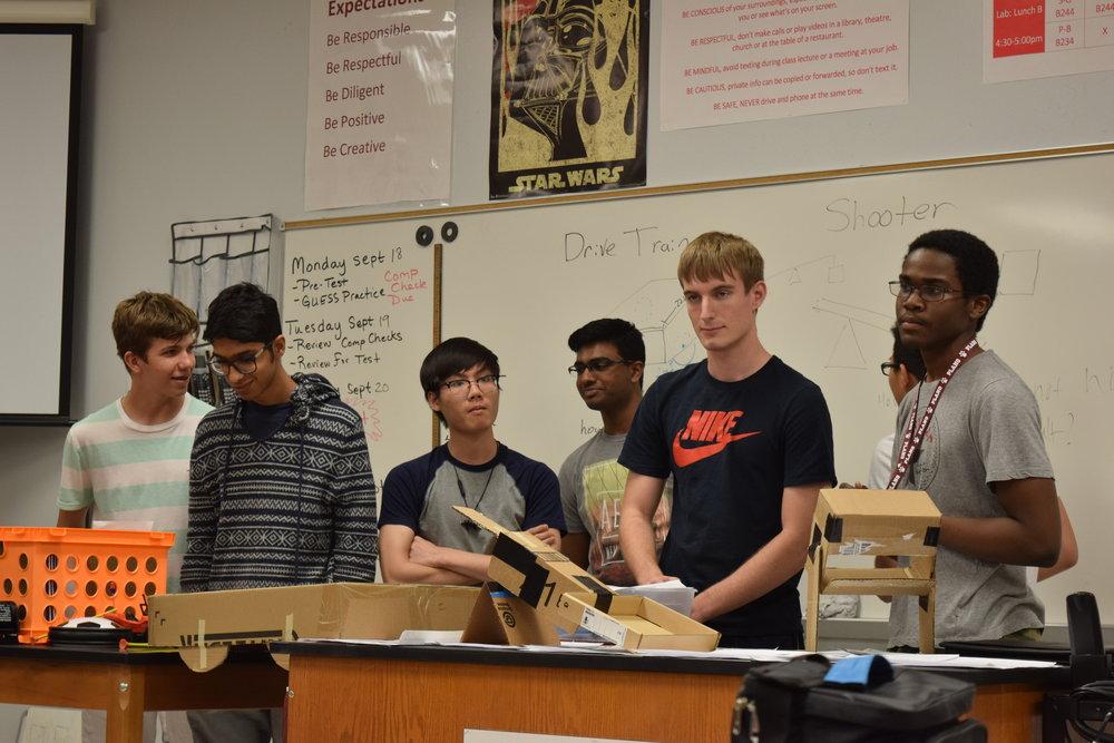 Team Rocket members explaining their manipulator mechanism to the team.