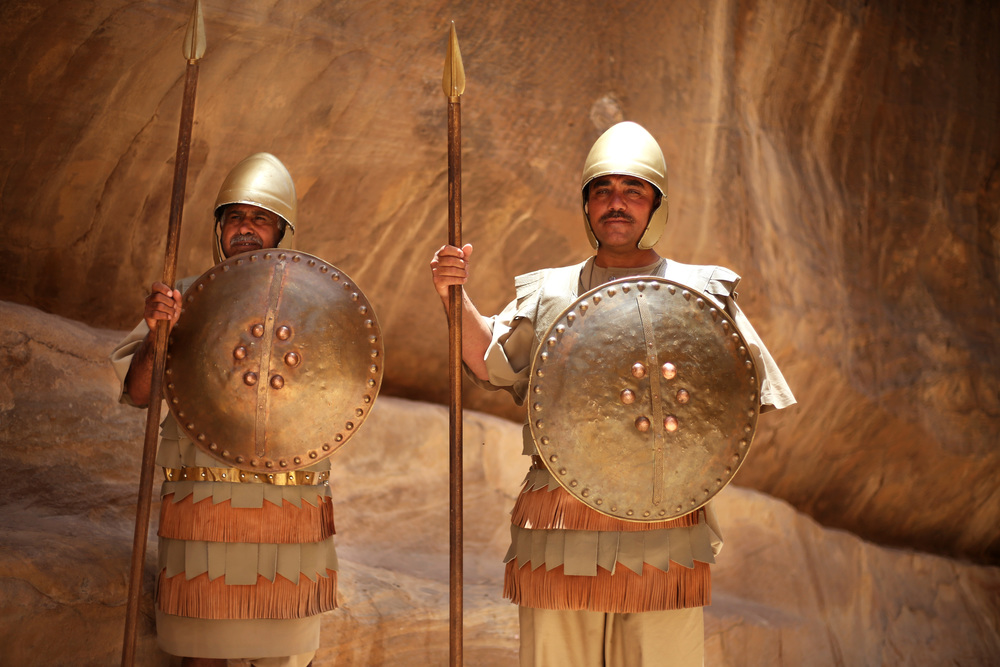 Jordanian guards pose in front of a canyon in Petra, Jordan, on June 8, 2016. This ancient city is well known for being carved into red desert cliffs and for the unique water conduit system.