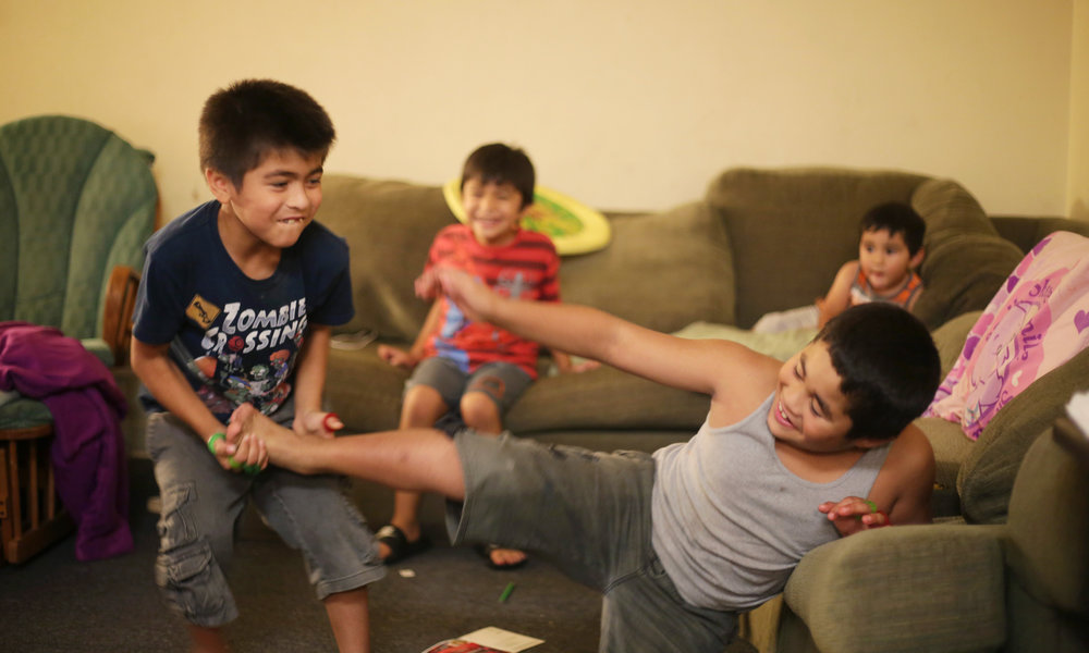 Jimmy, 7, and Ricky 9, Rios's sons wrestle each other in the living room in Pomona California, July 2016. Jimmy and Ricky both love being active and playing games with each other.