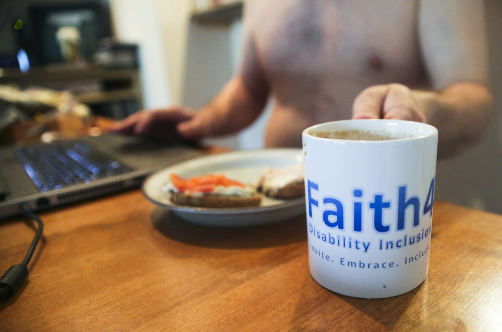 "Kevin Pettit, 50, reaches for his cup of coffee in the morning as he does some work for his organization Faith4All at his house in Boulder, Colorado, on May 1, 2018. Pettit created this organization organization in 2013 with the goal to get churches to be more accepting and accommodating to people with disabilities. Pettit said, ""I think that the meaning of my injury and why I am still alive is so that I could help other people with disabilities."""