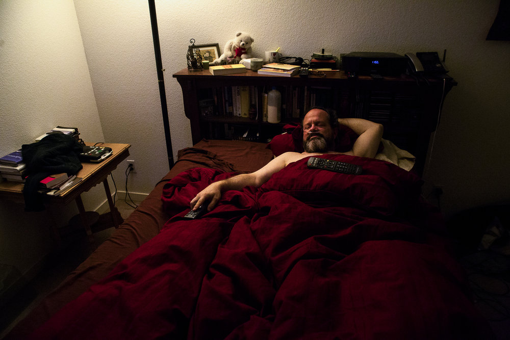 Kevin Pettit, 50, lies down and watches television before bed at his house in Boulder, Colorado, on April 10, 2018.