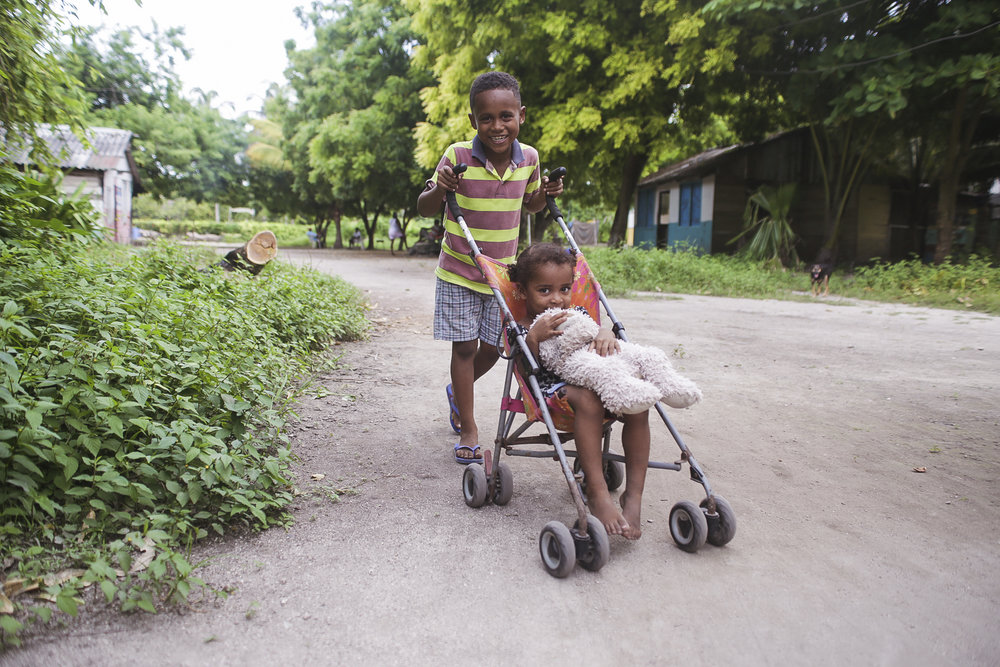 A little boy pushes his sister in a stroller around the Rosario Islands in Colombia on July, 10 2018. These kids were being playful and seeing how fast they could go around this dirt path.
