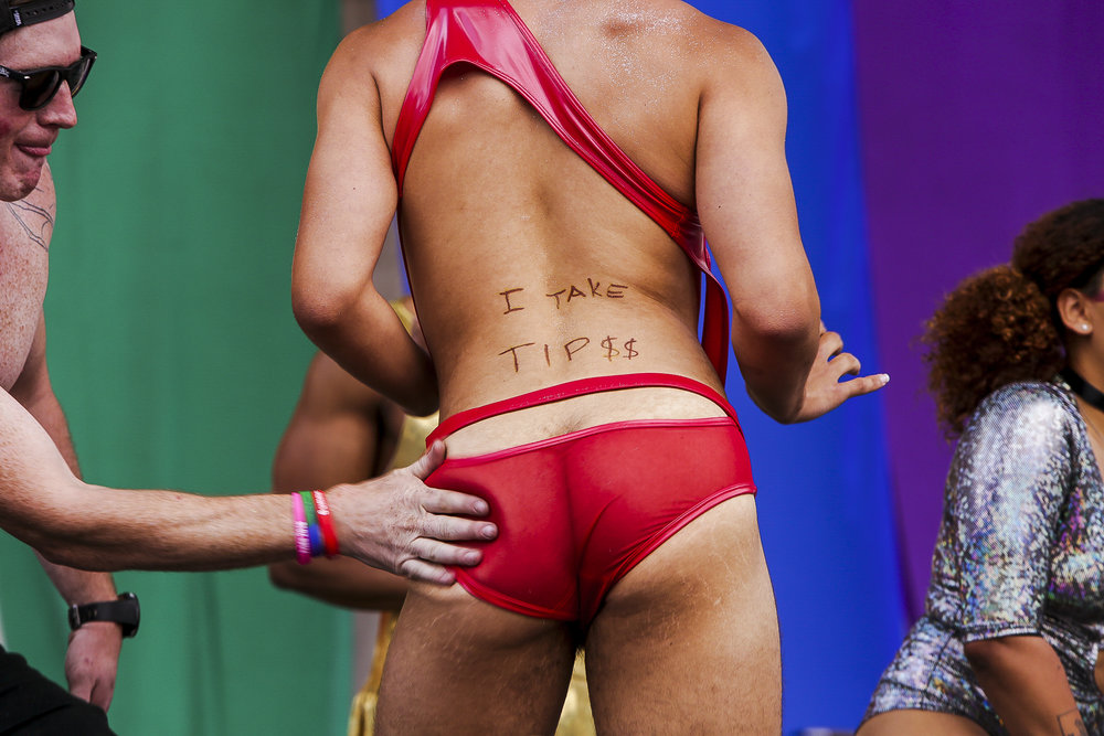 A guy slaps a participant's butt during a booty-shaking contest at Pride in Denver, Colorado, on June 17, 2018.